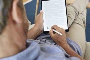 Hombre firmando digitalmente en una tablet desde casa